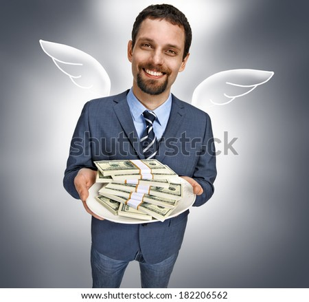 Business angel with money / happy smiling young businessman in a suit jacket offering stacks of US dollar bills - isolated on gray background  - stock photo
