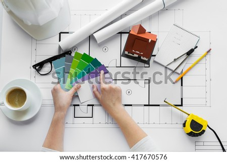 business, architecture, building, construction and people concept - close up of designer hands with color palette and house blueprint - stock photo