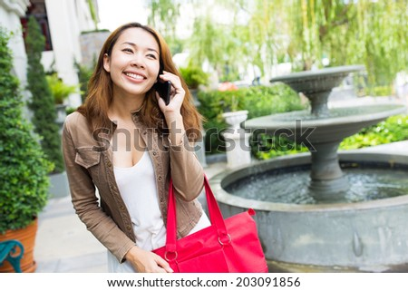Business asian woman using mobile smart phone at outdoors.