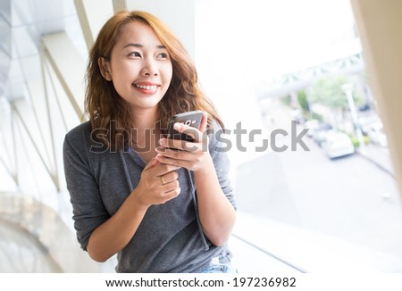Business asian woman using smart phone in the modern building - stock photo
