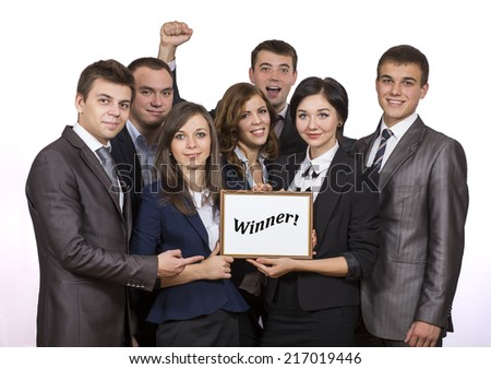 Business award. Business team is celebrating the award received. Seven young business team express bright emotions and keep the frame with WINNER sign. - stock photo