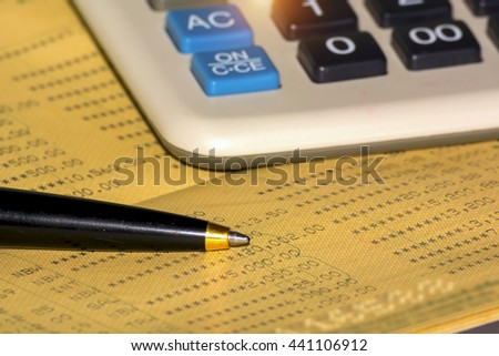 Business background,Bank account passbook with pen and calculator - stock photo