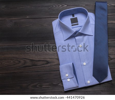 Business background - blue shirt and necktie on black  table. Top view. Copy space - stock photo