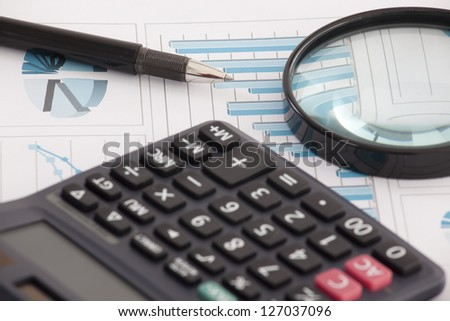 Business background, financial data concept with pen and magnifying glass