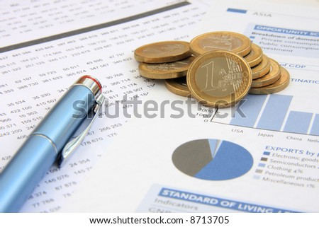 Business background: Financial reports, euro coins and a blue pen (focus on the coins)
