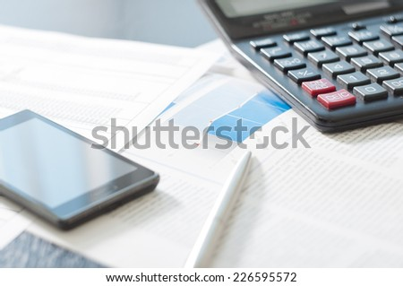 Business background with calculator pen and black phone - stock photo