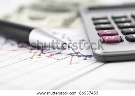 Business background with charts, pen and calculator - stock photo