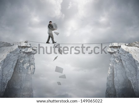 Business Balance - A businessman carrying paperwork walking over a tight rope. - stock photo