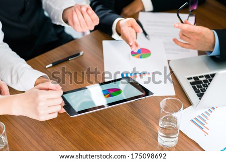 Business - banker, Manager or expert in meeting evaluates the figures on tablet computer and compares the development of the business to advise and act as consultant - stock photo