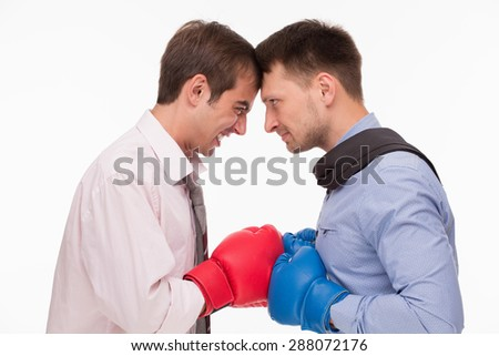 Business battle between two men about corporations. Two men in boxing gloves their heels in. - stock photo