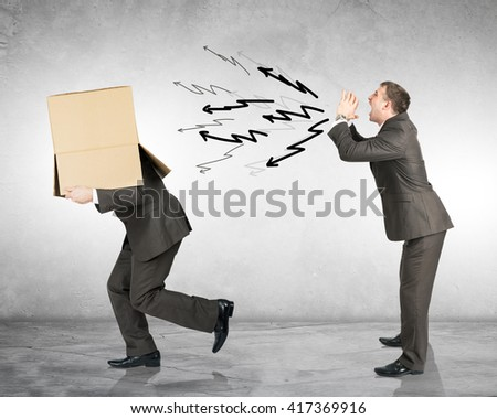 Business boss shouting to employee with box on his head - stock photo