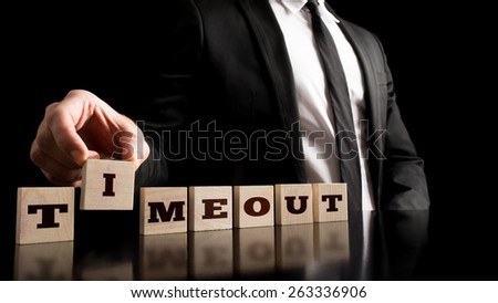 Business Break Concept - Businessman Arranging Small Wooden Blocks with word Timeout on a Pure Black Background. - stock photo