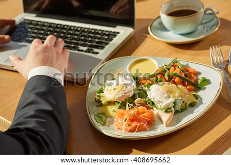 Business breakfast. Cropped closeup of a breakfast toasts with eggs and salad plate on the table near businessman working on his laptop - stock photo