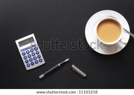 business breakfast in the office on black desktop with calculator pen and glasses