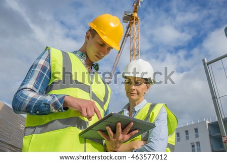 business, building, paperwork and people concept - builder in hardhat with tablet outdoors