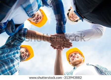 business, building, partnership, gesture and people concept - close up of smiling builders in hardhats with hands on top outdoors - stock photo