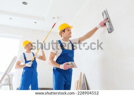 business, building, teamwork and people concept - group of smiling builders in hardhats with plastering tools indoors - stock photo