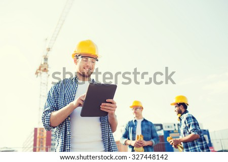 business, building, teamwork, technology and people concept - group of smiling builders in hardhats with tablet pc computer outdoors - stock photo