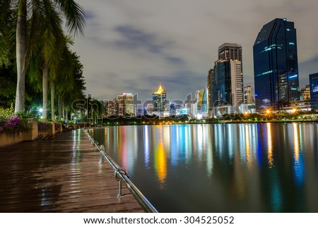 Business buildings in Bangkok seen from Benjakiti park, night Scene, Thailand - stock photo
