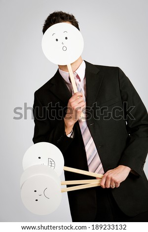 Business: Businessman Hiding Behind Masks - stock photo