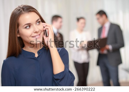Business calls. Confident beautiful female manager talking over the phone with a smile while her colleagues standing in blurry on the background - stock photo