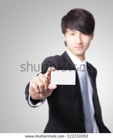business card in business man hand with smile face ( focus on paper ) isolated on gray background, asian male model - stock photo