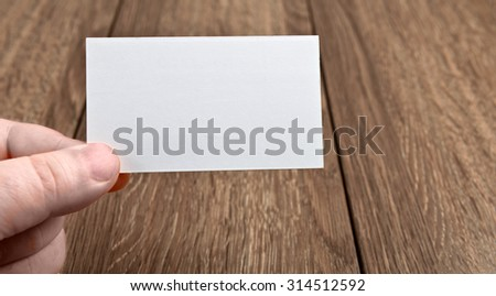 Business card in hand over wooden table - stock photo