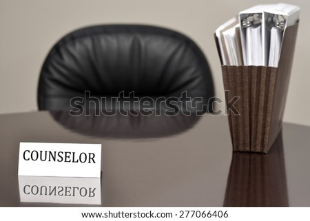 Business card on desk for counselor to provide help advice with files and chair - stock photo
