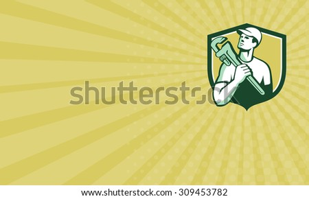Business card showingillustration of a tradesman plumber holding adjustable monkey wrench on shoulder looking up to the side set inside shield crest on isolated background done in retro style.  - stock photo