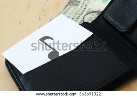 Business card with the sign NOTE in wallet with dollars   - stock photo
