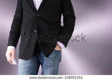 business casual man with a relaxed stance holding a business card with a stainless backdrop (shallow depth of field) - stock photo