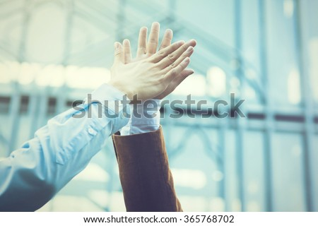 Business celebration for good teamwork with a high-five (Vintage Tone) - stock photo