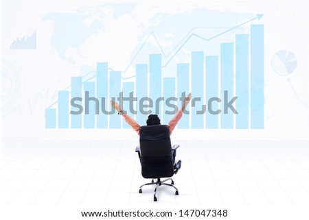 Business CEO sitting on a chair with his arms raised looking at profitable bar chart on world map