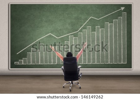 Business CEO with his arms raised looking at profit bar chart on chalkboard - stock photo