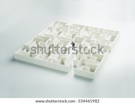 Business challenge. A businessman navigating through a maze. Front view - stock photo