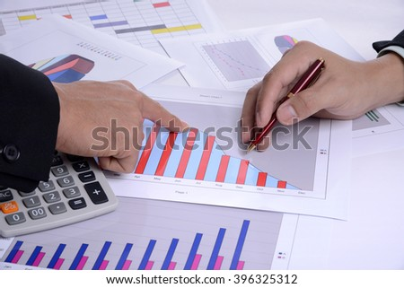 Business chart and two hands of businessman on meeting table