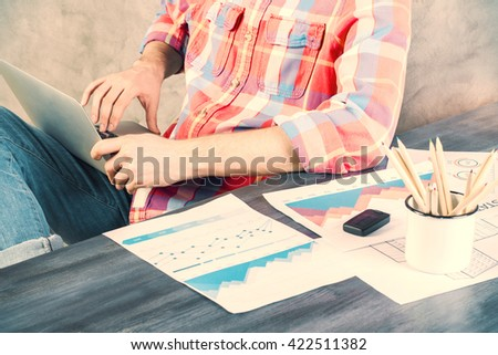 Business charts and graphs on wooden office desk with caucasian male using laptop next to it - stock photo