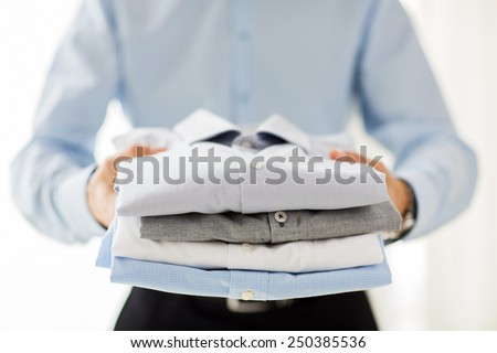 business, clothing and people concept - close up of businessman holding folded shirts - stock photo