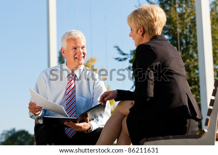 Business coaching outdoors - a man and a woman have a coaching discussion