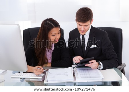 Business colleagues calculating tax together at desk in office