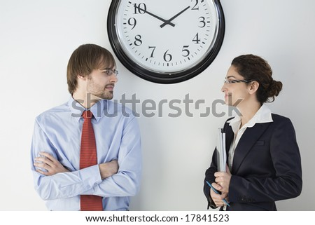 Business colleagues conversing near wall clock