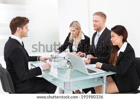Business colleagues discussing at desk in office - stock photo