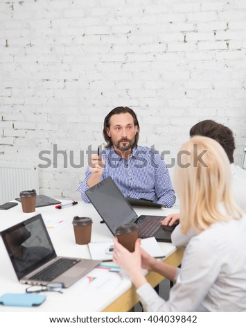 Business colleagues discussing business projects and strategies in office. Serious man expressing his opinion. - stock photo