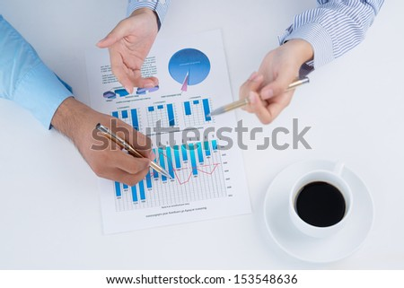 Business colleagues discussing the financial graphics viewed below - stock photo