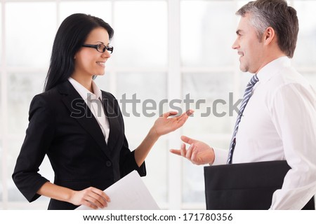 Business colleagues discussing work. Two cheerful business people discussing something and gesturing while standing face to face  - stock photo