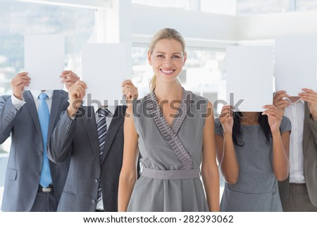 Business colleagues hiding their face with paper in the office - stock photo