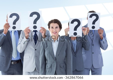 Business colleagues hiding their face with question mark sign against blue vignette background - stock photo