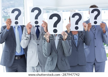 Business colleagues hiding their face with question mark sign at the office - stock photo