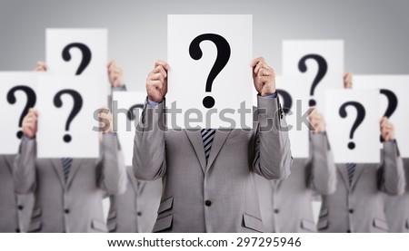 Business colleagues holding question mark signs in front of their faces concept for recruitment, confusion or questionnaire