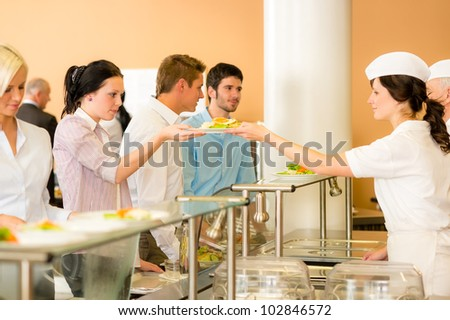 Business colleagues in cafeteria lunch-lady serve fresh healthy food meals - stock photo